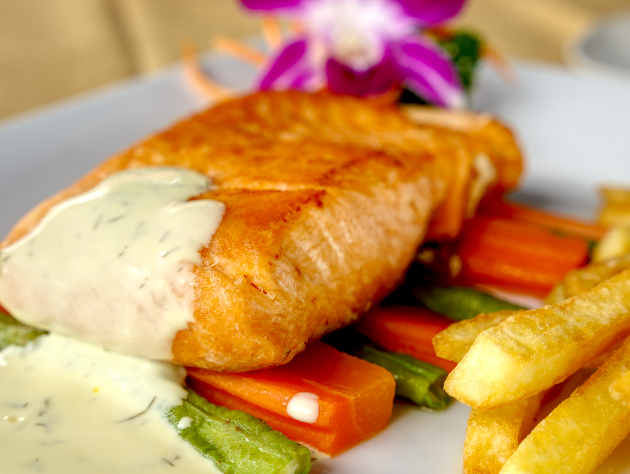 photograph of pan fried salmon steak with vegetables and french fries